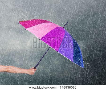 Hand Holding Multicolored Umbrella Under Dark Sky With Rain