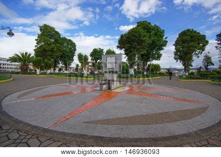 TULCAN, ECUADOR - JULY 3, 2016: cardinal points monument in the middle of the park with some trees as background.