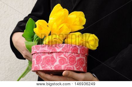 Man in black suit with flowers and gift box