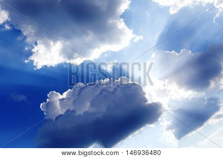 Sky with bright sun behind dark storm clouds