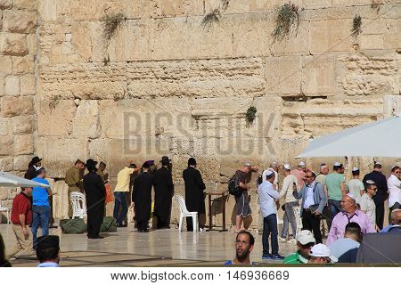 JERUSALEM, ISRAEL, OCTOBER 24, 2013, Jewish  rabbi along with other worshipers praying at the mens side of the Western Wailing Wall which is also known as the Kotel, the most holy site for Jews in Jerusalem, Israel.