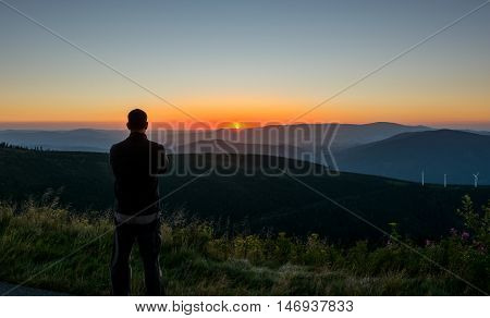 Man looking to sunset over Czech mountains Jeseniky