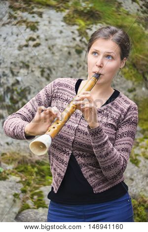 Young woman playing hornpipe (birbyne)Lithuanian aerophone that can be either single or double-reeded and may or may not have a mouthpiece.