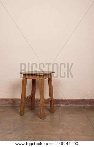 Rustic wooden stool, pink wall background