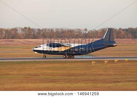 Kiev Region Ukraine - October 23 2011: Antonov An-12 cargo plane is touching down on the runway on sunset