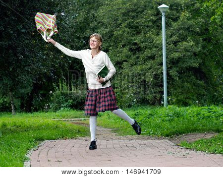 Happy school girl in the park. Girl in school uniform running of the school. Book school bag