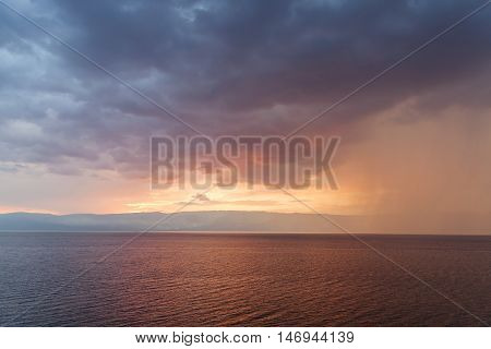 Rain storms are happening at sea on sunset sky