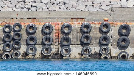 Old concrete mooring wall with car tires
