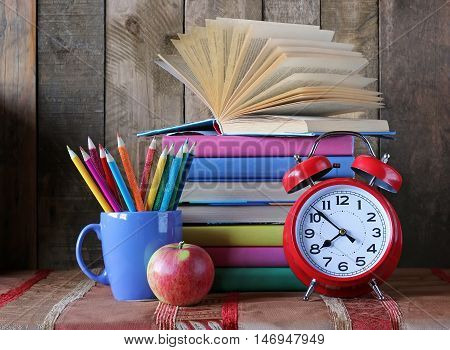 Back to school. A stack of books crayons Apple and clock on the table. Still life with books. School books in colorful covers.