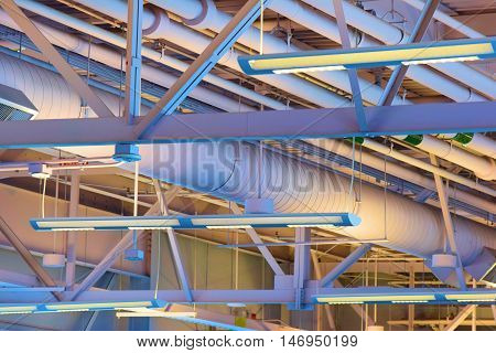 Ceiling Pipes with hanging lamps taken inside a warehouse