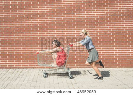 two female having fun with a shopping cart at the mall parking lot
