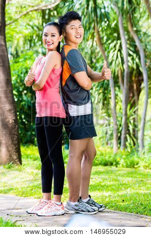 Asian Chinese man and woman take a break after fitness jogging in city park