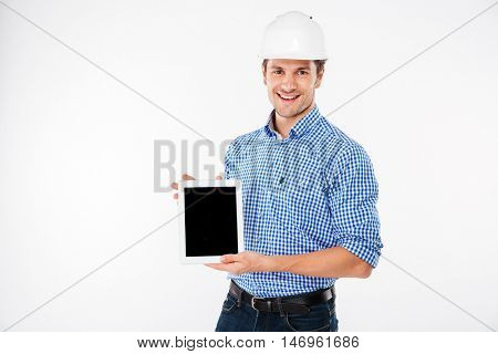 Happy young man architect in building helmet holding blank screen tablet