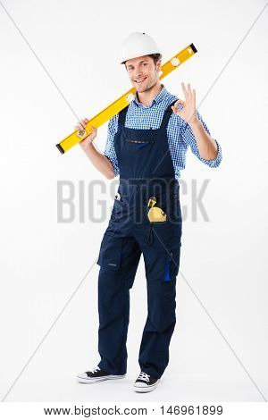 Full length portrait of a smiling male builder standing and showing okay gesture isolated on a white background