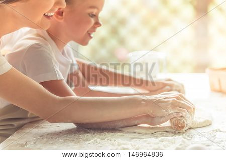 Side view of cute little girl and her beautiful mom in aprons smiling while flattening the dough using a rolling pin in the kitchen cropped