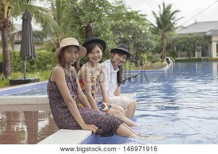 younger asian woman friend relaxing happiness emotion at water pool