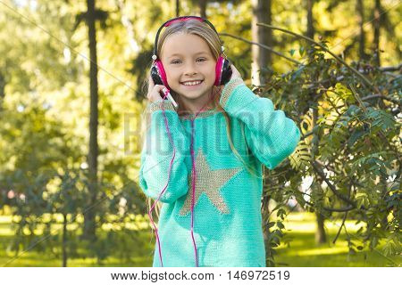Girl With Headphones Having Fun In The Park . She Was Fun And She's Happy . Good Music In The Headph