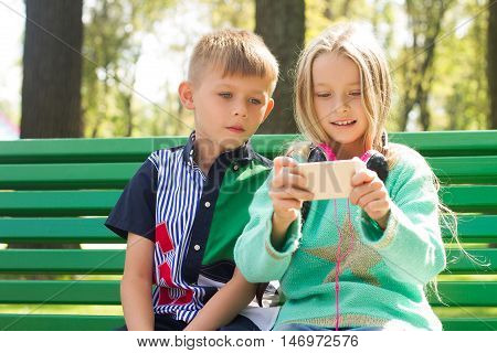 Boy and girl looking at the phone .They look very enthusiastically . Children and technology