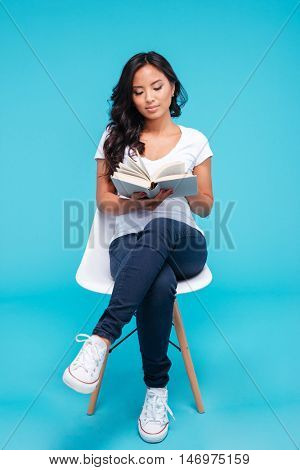 Pensive young attractive vietnamese girl reading book and sitting on chair isolated on the blue background