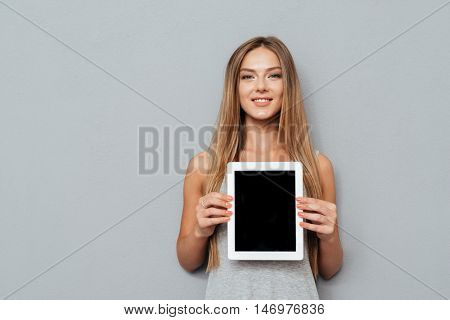 Smiling casual woman showing blank tablet computer screen isolated on a gray background