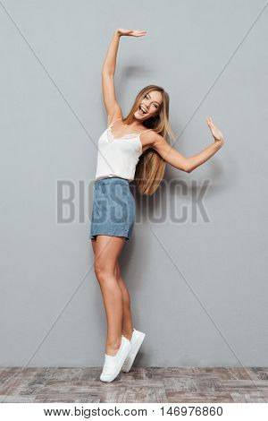 Full length portrait of a beautiful smiling woman posing on her tiptoes isolated on a gray background