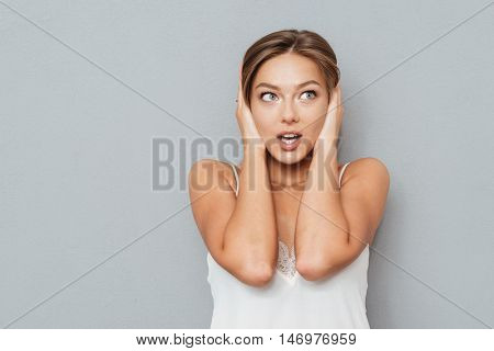 Casual young cute woman covering her ears isolated on a gray background