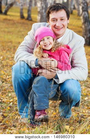 Father playing with daughter at autumn. Family outdoors