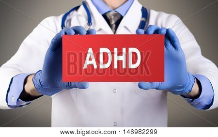 Doctor's hands in blue gloves shows the word ADHD (attention deficit hyperactivity disorder). Medical concept.