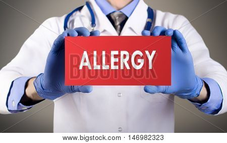 Doctor's hands in blue gloves shows the word allergy. Medical concept.