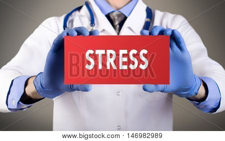 Doctor's hands in blue gloves shows the word stress. Medical concept.