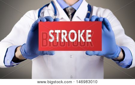Doctor's hands in blue gloves shows the word stroke. Medical concept.