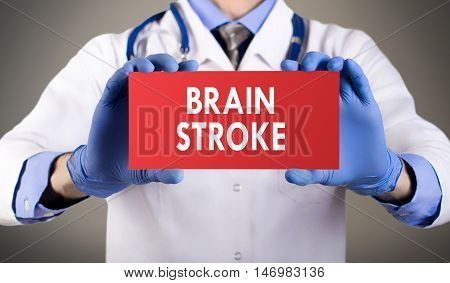 Doctor's hands in blue gloves shows the word brain stroke. Medical concept.