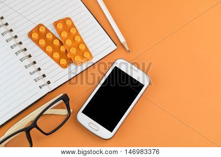 Office Desk Table With  Smartphone,blank Spiral Notebook,  Glasses ,white Pencil And Orange Blisters