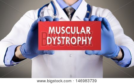 Doctor's hands in blue gloves shows the word muscular dystrophy. Medical concept.