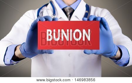 Doctor's hands in blue gloves shows the word bunion. Medical concept.