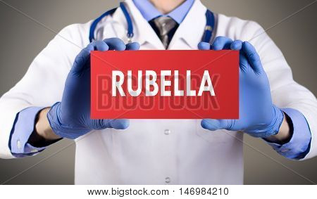 Doctor's hands in blue gloves shows the word rubella. Medical concept.