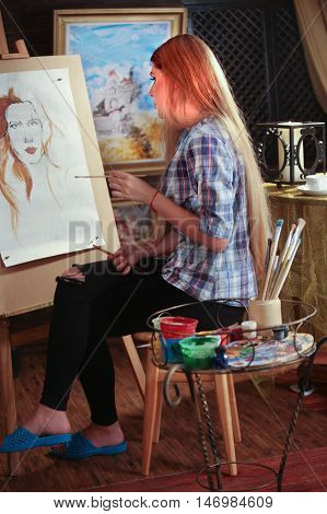Girl artist paints portrait of woman with pencil. Girl painter throw leg over other. Girl paints by pencil on easel. Pictures on background.