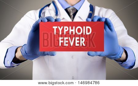 Doctor's hands in blue gloves shows the word typhoid fever. Medical concept.