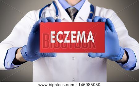 Doctor's hands in blue gloves shows the word eczema. Medical concept.
