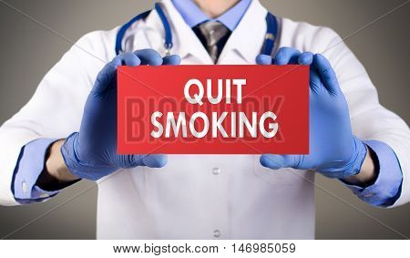 Doctor's hands in blue gloves shows the word quit smoking. Medical concept.