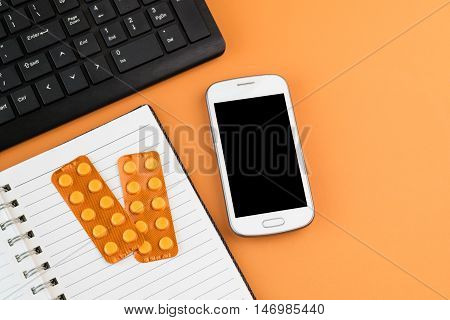 Office desk table with white smart phone black computer keyboard blank spiral notebook and orange blisters of pharmaceutical pills on orange desk background