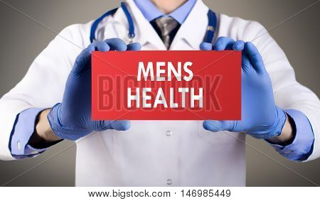 Doctor's hands in blue gloves shows the word mens health. Medical concept.