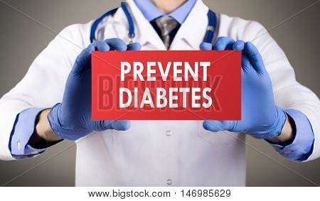 Doctor's hands in blue gloves shows the word prevent diabetes. Medical concept.