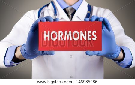 Doctor's hands in blue gloves shows the word hormones. Medical concept.