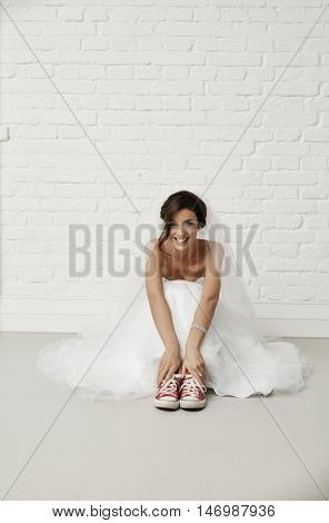 Happy smiling bride sitting on floor in red sneakers and white wedding gown.