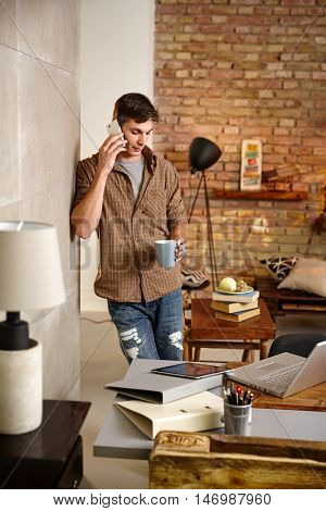 Young man leaning against wall at home, talking on mobilephone, drinking tea.