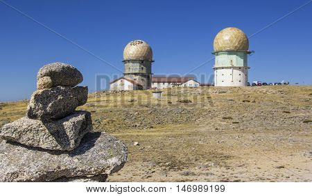 background view of two round towers on the top of a mountain in the nature reserve of Sierra de Eshtrella, Portugal