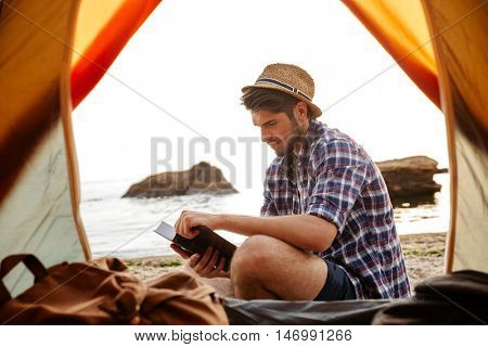 Smiling young man sitting near touristic tent and reading book at the beach