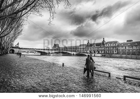 Seine river and Orsay Museum in monochrome settings - Black and white image with the Seine River its shore where people walk an old bridge and the Orsay Museum under a dramatic sky on a chilly day of February.