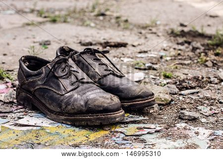 Conceptual shooting of homeless man dirty shoes left on the street